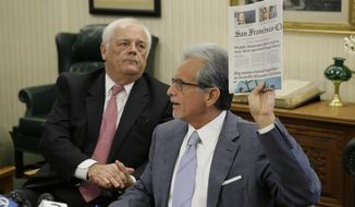 Attorney Frank Pitre holds up a newspaper headline with Pacific Gas and Electric saying that someone else's wires may have started the last month's wildfires during a news conference Tuesday, Nov. 14, 2017, in Burlingame, Calif. Looking on at left is attorney Mike Kelly. Five law firms have filed a series of lawsuits against PG&E Corporation and Pacific Gas & Electric Company on behalf of wildfire victims Filed in San Francisco Superior Court on Tuesday, the plaintiffs include former San Francisco Mayor Frank Jordan and his wife who fled the fire and lost their Santa Rosa home, and Gregory and Christina Wilson who sought refuge in their swimming pool in an effort to avoid being burned by the fire. (AP Photo/Eric Risberg)
