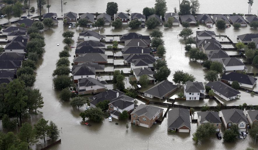 FILE - In this Tuesday, Aug. 29, 2017, file photo, homes are surrounded by floodwaters from Tropical Storm Harvey in Spring, Texas. The House has passed legislation that will increase flood insurance premiums for many property owners to help firm up a program under stress from ever-more frequent and powerful storms. (AP Photo/David J. Phillip, File)