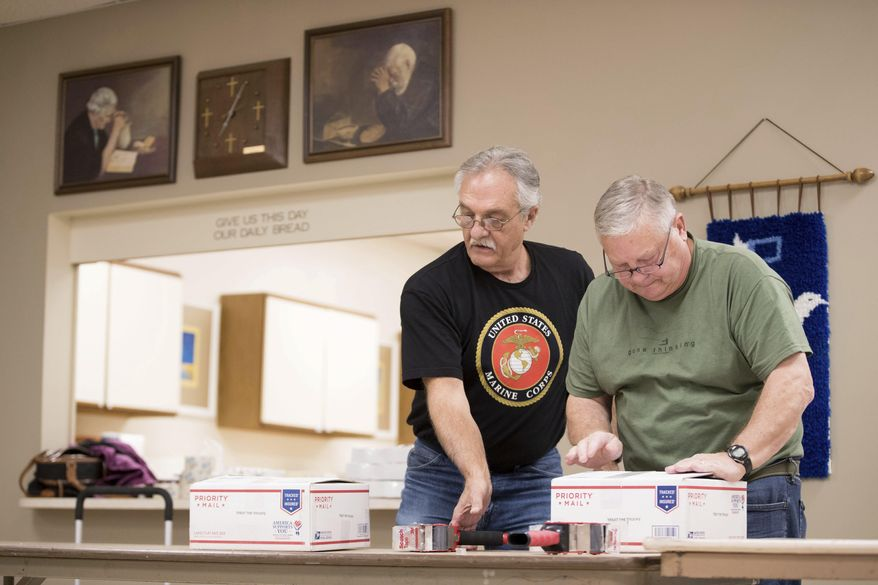 Nick Nicotero, left, and Mike Crawford help pack care packages with the Iowa Cookie Crumbs for US military serving overseas Monday, Nov. 6, 2017 in Council Bluffs, Iowa.  The group is scrambling to package and mail at least 30,000 cookies abroad to U.S. service members in an annual effort aimed at improving morale for those serving overseas during the holidays.  (Julia Nagy/Omaha World-Herald via AP)