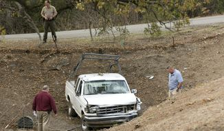 """Investigators view a pickup truck involved in a deadly shooting rampage at the Rancho Tehama Reserve, near Corning, Calif., Tuesday, Nov. 14, 2017. A gunman driving stolen vehicles and choosing his targets at random opened fire """"without provocation"""" in the tiny, rural Northern California town Tuesday, killing several people, including a student at an elementary school, before police shot him dead, authorities said. (AP Photo/Rich Pedroncelli)"""