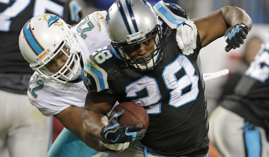 Carolina Panthers' Jonathan Stewart (28) is tackled by Miami Dolphins' T.J. McDonald (22) in the second half of an NFL football game in Charlotte, N.C., Monday, Nov. 13, 2017. (AP Photo/Bob Leverone)