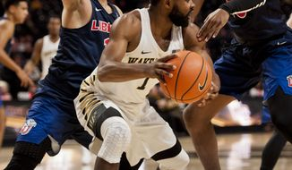 Liberty's Georgie Pacheco-Ortiz, left, and Isaiah Williams double-team Wake Forest's Keyshawn Woods during the first half of an NCAA college basketball game, Tuesday, Nov. 14, 2017, in Winston-Salem, N.C. (Walt Unks/Winston-Salem Journal via AP)