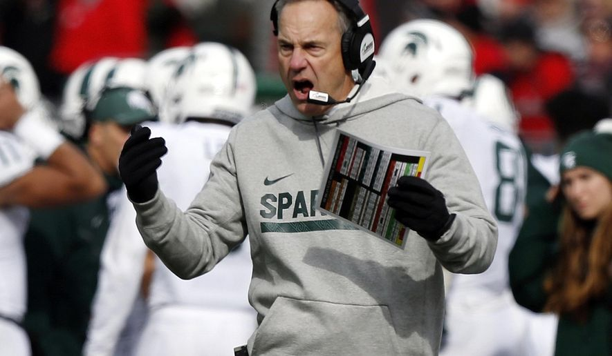 FILE - In this Saturday, Nov. 11, 2017, file photo, Michigan State head coach Mark Dantonio cheers his team on against Ohio State during the first half of an NCAA college football game in Columbus, Ohio. After working its way into the Big Ten title chase, Michigan State received a harsh reminder of the gap between the Spartans and Ohio State.(AP Photo/Jay LaPrete, File)