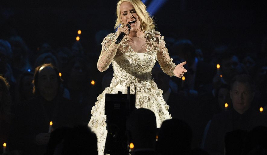 """FILE - In this Wednesday, Nov. 8, 2017, file photo, Carrie Underwood performs """"Softly and Tenderly"""" during an In Memoriam tribute at the 51st annual CMA Awards at the Bridgestone Arena in Nashville, Tenn. In a statement Sunday, Nov. 12, on Twitter, Underwood thanked her fans for messages of support following a fall on steps outside her home on Friday. (Photo by Chris Pizzello/Invision/AP, File)"""