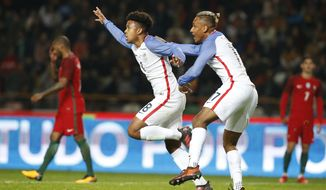 U.S. player Weston McKennie, centre left, celebrates with U.S. player Juan Agudelo after scoring the opening goal during an international friendly soccer match between Portugal and U.S. at the Dr. Magalhaes Pessoa stadium in Leiria, Portugal, Tuesday Nov. 14, 2017. (AP Photo/Pedro Rocha)