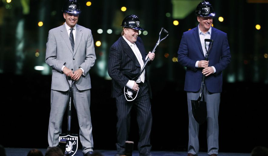 Oakland Raiders owner Mark Davis, center, pretends to play air guitar beside Nevada Gov. Brian Sandoval, left, and NFL Commissioner Roger Godell during a ceremonial groundbreaking for the Raiders' stadium Monday, Nov. 13, 2017, in Las Vegas. After years of planning, dealing and getting millions in public financing approved, the team broke ground on a 65,000-seat domed stadium in Las Vegas, across the freeway from the city's world-famous casinos. (AP Photo/John Locher)