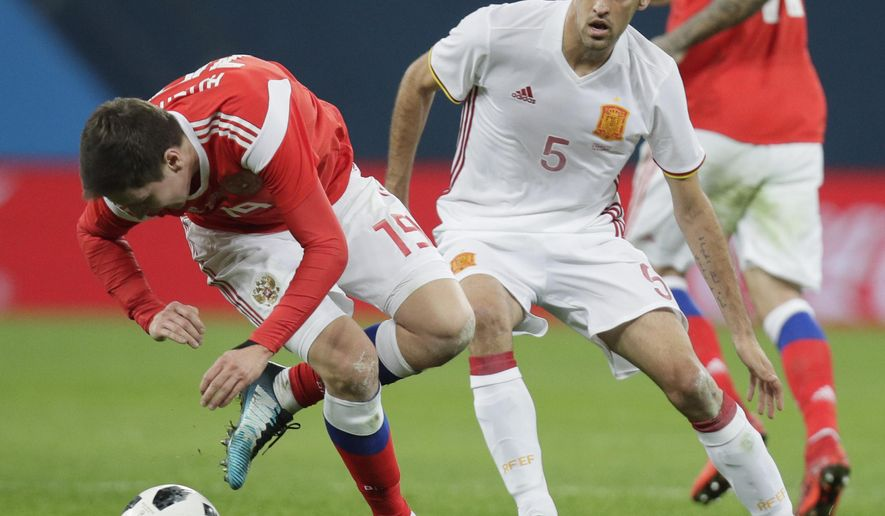 Russia's Daler Kuzyayev, left, struggles for the ball with Spain's Sergio Busquets during the international friendly soccer match between Russia and Spain in St.Petersburg, Russia, Tuesday, Nov. 14, 2017. (AP Photo/Dmitri Lovetsky)