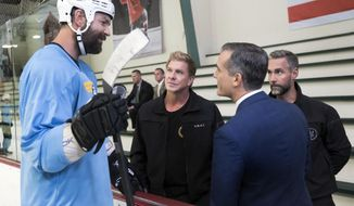 In this image taken Sept. 26, 2017 and released by CBS Entertainment, from left, former NHL hockey player John Scott, speaks with actor Kenny Johnson, Los Angeles Mayor Eric Garcetti and actor Jay Harrington during the filming of an episode of the CBS series S.W.A.T at the Pickwick Center in Burbank, Calif. Enforcer turned NHL All-Star, Scott tried out acting, and it made him more nervous than fighting 250-pound rivals and playing in front of 20,000 fans. Maybe that's not his next career, but with a movie coming out, Scott is considering his next move. (Monty Brinton/CBS Entertainment via AP)