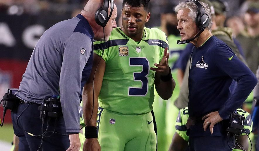 FILE - In this Thursday, Nov. 9, 2017, file photo, Seattle Seahawks quarterback Russell Wilson (3) speaks with head coach Pete Carroll, right, and assistant head coach Tom Cable during an NFL football game against the Arizona Cardinals in Glendale, Ariz. The Seahawks return to practice Tuesday, Nov. 14, 2017, without Richard Sherman and facing questions about how the team handled the concussion protocol with quarterback Russell Wilson. (AP Photo/Rick Scuteri, File)