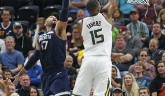 Utah Jazz forward Derrick Favors (15) shoots as Minnesota Timberwolves forward Taj Gibson (67) defends in the first half during an NBA basketball game Monday, Nov. 13, 2017, in Salt Lake City. (AP Photo/Rick Bowmer)
