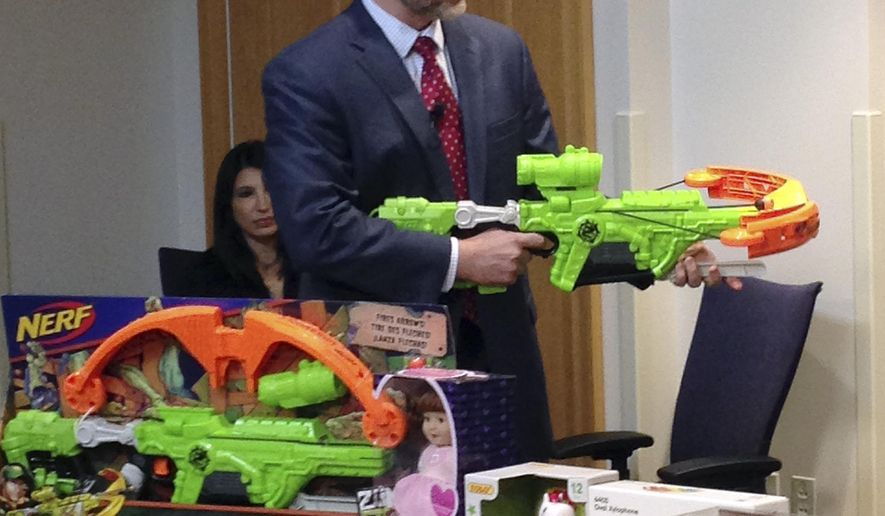 """James Swartz, director of World Against Toys Causing Harm, or W.A.T.C.H., displays Nerf's """"Zombie Strike"""" crossbow during a news conference Tuesday, Nov. 14, 2017, in Boston, where the child safety group released its annual holiday list of the 10 most hazardous toys. (AP Photo/Philip Marcelo)"""