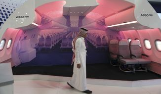 A man passes by an A330 neo mockup at the Airbus stand during the Airshow in Dubai, United Arab Emirates, Wednesday, Nov. 15, 2017. Airbus signed a $49.5 billion deal on Wednesday to sell 430 airplanes to the Phoenix-based private equity firm that owns Frontier Airlines, striking the European aerospace company's biggest deal ever at the Dubai Air Show. (AP Photo/Kamran Jebreili)