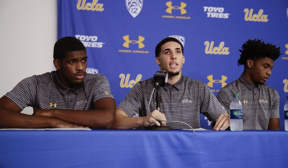Flanked by teammates Cody Riley, left, and Jalen Hill, UCLA basketball player LiAngelo Ball reads his statement during a news conference at UCLA Wednesday, Nov. 15, 2017, in Los Angeles. The three players were detained in Hangzhou following allegations of shoplifting last week before a game against Georgia Tech in Shanghai. (AP Photo/Jae C. Hong) **FILE**
