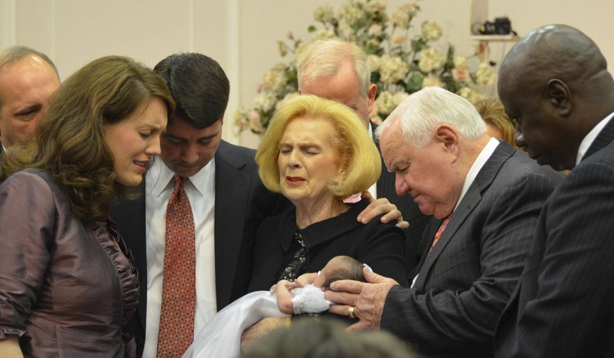 FILE - In this 2012 photo provided by a former member of the church, Word of Faith Fellowship leader Jane Whaley, center, holds a baby with her husband, Sam, center right, and others during a ceremony in the church's compound in Spindale, N.C. Under the leadership of Jane Whaley, the controversial church has grown to about 750 congregants in Spindale and a total of nearly 2,000 members worldwide. (AP Photo)