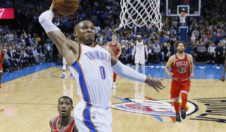 Oklahoma City Thunder guard Russell Westbrook (0) goes up for a dunk in front of Chicago Bulls guard Kris Dunn, left, and center Robin Lopez (42) in the second quarter of an NBA basketball game in Oklahoma City, Wednesday, Nov. 15, 2017. (AP Photo/Sue Ogrocki)