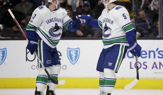Vancouver Canucks left wing Sven Baertschi, left, celebrates hisp goal with defenseman Derrick Pouliot during the third period of an NHL hockey game against the Los Angeles Kings in Los Angeles, Tuesday, Nov. 14, 2017. The Canucks won 3-2. (AP Photo/Chris Carlson)