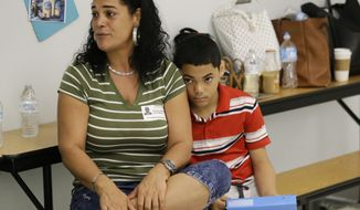 In this Tuesday, Nov. 14, 2017, photo, recent transplant from Puerto Rico, Arieliss Valencia sits next to her son Anthony, right, a fifth grader at Riverdale Elementary School after school supplies were handed out to the students in Orlando, Fla. Anthony left Puerto Rico with his family for central Florida after Hurricane Maria destroyed his home. He is living with relatives and has been welcomed into Orlando's Riverdale Elementary School. (AP Photo/John Raoux)