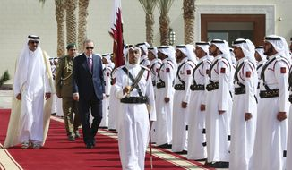 Turkey's President Recep Tayyip Erdogan, left, centre, walks with the Emir of Qatar Sheikh Tamim bin Hamad Al Thani, left, as they review an honour guard during the welcome ceremony prior to the meeting in Doha, Qatar, Wednesday, Nov. 15, 2017. Erdogan is in a two day tour in the Middle East, that also took him to Kuwait. (Kayhan Ozer, Pool via AP)