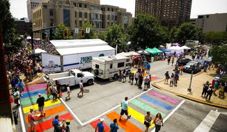In this Saturday, June 24, 2017 photo, pedestrians use the rainbow crosswalks at the corner of North Limestone Street and Short Street during the 10th annual Lexington Pride Festival at the Robert F. Stephens Courthouse Plaza in Lexington, Ky. The rainbow-colored crosswalk honoring the LGBT community in Lexington is a distracting safety hazard and should be removed, a federal official says. Officials painted the crosswalk at the busy intersection across from the county courthouse earlier this year to coincide with the annual gay pride festival. At the time, city officials said the crosswalk would be safer because it would better catch the attention of drivers.  (Alex Slitz/Lexington Herald-Leader via AP)