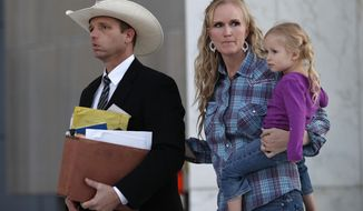 Ryan Bundy, left, walks out of federal court with his wife Angela Bundy, Tuesday, Nov. 14, 2017, in Las Vegas. Ryan Bundy, along with his father Cliven Bundy, brother Ammon Bundy, and co-defendant Ryan Payne, are accused of leading an armed standoff in 2014 against government agents in a cattle grazing dispute. (AP Photo/John Locher)