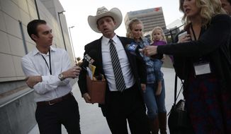 Ryan Bundy, center, walks out of federal court with his wife Angela Bundy, Tuesday, Nov. 14, 2017, in Las Vegas. Ryan Bundy, along with his father Cliven Bundy, brother Ammon Bundy, and co-defendant Ryan Payne, are accused of leading an armed standoff in 2014 against government agents in a cattle grazing dispute. (AP Photo/John Locher)