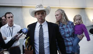 Ryan Bundy, center, walks out of federal court with his wife Angela Bundy, Tuesday, Nov. 14, 2017, in Las Vegas. (AP Photo/John Locher) ** FILE **