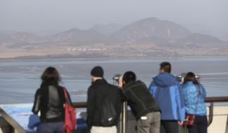 In this Nov. 14, 2017, photo, foreign visitors watch the North Korea side from the unification observatory in Paju, South Korea. South Korea says it will deport an American man detained for allegedly attempting to cross the mine-strewn border into North Korea. (AP Photo/Lee Jin-man)