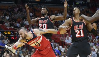 Washington Wizards' Marcin Gortat (13) is fouled by Miami Heat's Justise Winslow (20) during the first half of an NBA basketball game, Wednesday, Nov. 15, 2017, in Miami. At right is Miami Heat's Hassan Whiteside (21). (AP Photo/Lynne Sladky)