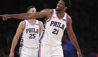 Philadelphia 76ers center Joel Embiid, right, gestures toward actor Kevin Hart after scoring as guard Ben Simmons stands in the background during the second half of an NBA basketball game against the Los Angeles Lakers, Wednesday, Nov. 15, 2017, in Los Angeles. The 76ers won 115-109. (AP Photo/Mark J. Terrill)