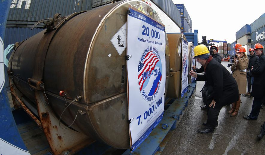 Representatives of participating companies sign containers with uranium to be used as fuel for nuclear reactors, prior to loading them aboard Atlantic Navigator ship,  on a port in St. Petersburg, Russia, Thursday, Nov. 14, 2013. A 20-year program to convert highly enriched uranium from dismantled Russian nuclear weapons into fuel for U.S. power plants has ended, with the final shipment loaded onto a vessel in St. Petersburg's port on Thursday. The U.S. Energy Department described the program, commonly known as Megatons to Megawatts, as one of the most successful nuclear nonproliferation partnerships ever undertaken. (AP Photo/Dmitry Lovetsky)