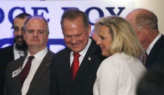 Former Alabama Chief Justice and U.S. Senate candidate Roy Moore arrives for a news conference, Thursday, Nov. 16, 2017, in Birmingham, Ala, with his wife Kayla Moore, right. (AP Photo/Brynn Anderson) **FILE**