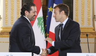 In this Sept. 1 2017 file photo, French President Emmanuel Macron, right, shakes hands with Lebanese Prime Minister Saad Hariri during a joint press conference at the Elysee Palace in Paris. Hariri has accepted an invitation to come to France after his surprise resignation from Saudi Arabia nearly two weeks ago that stunned Lebanon and rattled the region, the French president's office announced Thursday Nov. 16, 2017. (Ludovic Marin, Pool via AP, File)