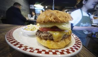 A 100 percent U.S. Angus beef Colby Jack Cheeseburger as part of U.S. President Donald Trump set is seen at Munch's Burger Shack restaurant in Tokyo Thursday, Nov. 16, 2017. The cheeseburger Trump had during his recent visit to Japan is still drawing lines at the Tokyo burger joint. (AP Photo/Eugene Hoshiko)
