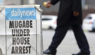 A person passes a newspaper headline in Harare, Zimbabwe, Thursday, Nov. 16, 2017. People across the country are starting another day of uncertainty amid quiet talks to resolve the country's political turmoil and the likely end of President Robert Mugabe's decades-long rule. Mugabe has been in military custody and there is no sign of the recently fired deputy Emmerson Mnangagwa, who fled the country last week. (AP Photo)