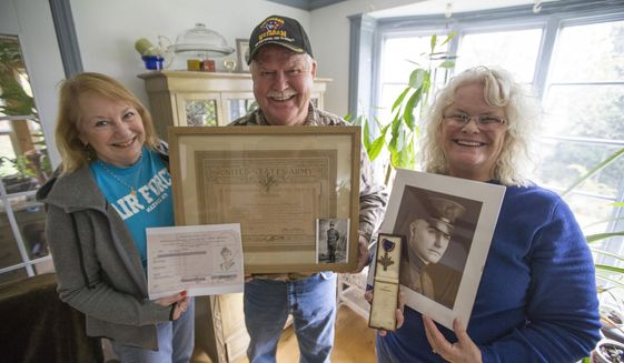 In this Nov. 7, 2017 photo, from left, Val Hunter, holding paperwork given to Gertrude  Hunter McDonald who served in World War 1, Michael Hunter, holding a Distinguished Service Award issued to David Hunter, Jr, and Kris Sommer, holding a picture of David Hunter, Jr and his Distinguished Service Cross, pose with the family's military awards in Rockford, Ill. The Hunter family has a long history of military service stretching back to the Civil War. (Arturo Fernandez/Rockford Register Star via AP)