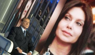 "Italian former Prime Minister and leader of ""Forza Italia"" party, Silvio Berlusconi, sits next to a portrait of his former wife Veronica Lario during the recording of Rai TV program 'Porta a porta', in Rome Thursday,  Nov. 16, 2017. (Claudio Peri/ANSA via AP)"