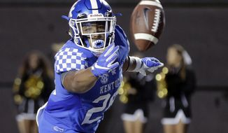 Kentucky running back Benny Snell Jr. tosses the ball to an official after scoring a touchdown on a 6-yard run against Vanderbilt in the second half of an NCAA college football game Saturday, Nov. 11, 2017, in Nashville, Tenn. (AP Photo/Mark Humphrey)