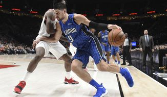 Orlando Magic center Nikola Vucevic drives to the basket around Portland Trail Blazers forward Ed Davis during the first half of an NBA basketball game in Portland, Ore., Wednesday, Nov. 15, 2017. (AP Photo/Steve Dykes)