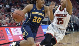 Michigan guard Deja Church (20) attempts to drive past the Louisville guard Asia Durr (25) during the first half of an NCAA college basketball game, Thursday, Nov. 16, 2017, in Louisville, Ky. (AP Photo/Timothy D. Easley)