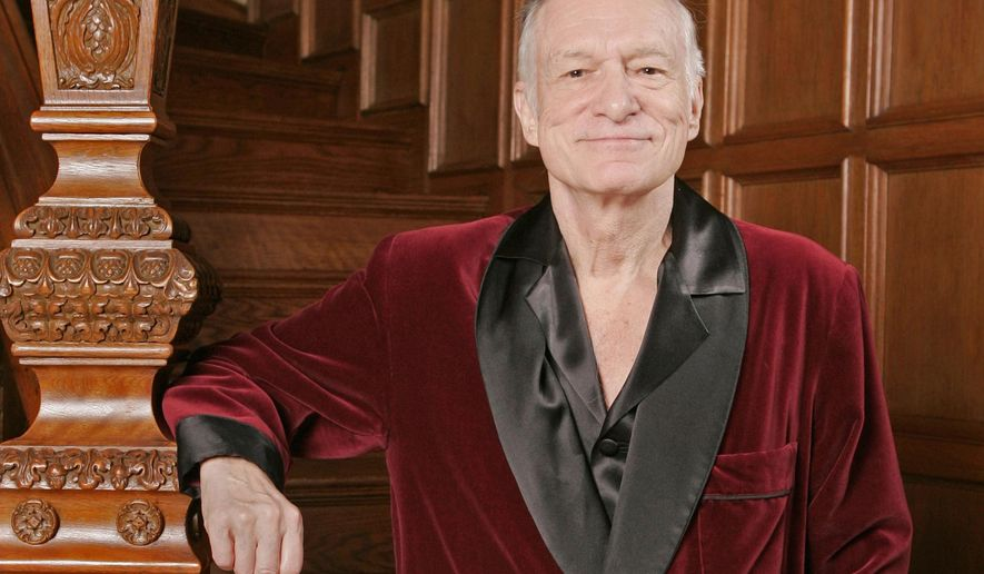 """FILE - In this April 7, 2006 file photo, Playboy founder Hugh Hefner poses at the Playboy Mansion in the Holmby Hills area of Los Angeles. Norman Lear, Cindy Crawford, Berry Gordy, Kim Basinger, Bill Maher and the Rev. Jesse Jackson are among the stars offering tributes to Hefner in a special edition of Playboy hitting newsstands this week. """"Celebrating Hef"""" chronicles the Playboy magazine founder's life in words and photos, with the celebrity essays highlighting Hefner's support for civil rights and first-amendment freedoms. (AP Photo/Kevork Djansezian, File)"""