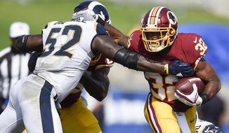 FILE - In this Sept. 17, 2017 file photo, Washington Redskins running back Samaje Perine (32) in action defended by Los Angeles Rams linebacker Alec Ogletree (52) during the second half of an NFL football game in Los Angeles. (AP Photo/Kelvin Kuo)