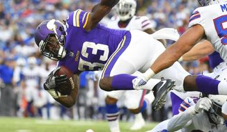 FILe - In this Aug. 10, 2017, file photo, Minnesota Vikings running back Dalvin Cook (33) leaps over Buffalo Bills' Trae Elston (36) during the first half of a preseason NFL football game in Orchard Park, N.Y. Cook is in the early stages of rehabilitation for his ACL reconstruction, but so far so good. He got rid of his crutches last week. (AP Photo/Rich Barnes, File)