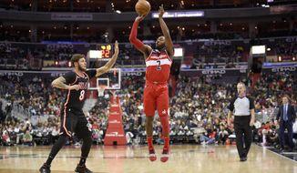 Washington Wizards guard John Wall (2) shoots against Miami Heat guard Tyler Johnson (8) during the second half of an NBA basketball game, Friday, Nov. 17, 2017, in Washington. (AP Photo/Nick Wass)