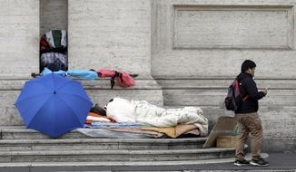 In this photo taken Thursday, Nov. 16, 2017, a man walks past a homeless sleeping on the steps of a building, in Rome. On the morning of Sunday, Nov. 19, 2017, Pope Francis will host some four thousand poor and vulnerable people in St Peter's Basilica and after a Mass 1.500 of the guests will have lunch with the him in the Paul VI hall in what the pontiff called World Day of the Poor. (AP Photo/Alessandra Tarantino)