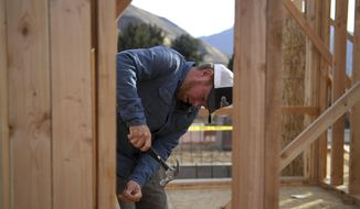 """In this Nov. 10, 2017, photo, Dustin Brinkerhoff, owner of Brinkerhoff Custom Construction, nails in a board to put in place as a temporary safety guard rail at a worksite of a future home in Mapleton, Utah. According to research by Ken Simonson, the chief economist for the Associated General Contractors of America, the construction industry is generally very robust. Utah sits in the middle of the pack, adding about 4,000 jobs in the past year. Brinkerhoff sees effects of labor shortage in """"every job, every day."""" (Isaac Hale/The Daily Herald via AP)"""