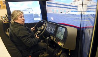 In this Thursday, Nov. 9, 2017 photo, Tami Yarnall, CDL instructor, demonstrates Schuylkill Technology Center's new TranSim VS6 truck driving simulator at the Schuylkill Technology Center's airport campus, at Schuylkill County Airport, Mount Pleasant, Pa. (David McKeown /Republican-Herald via AP)