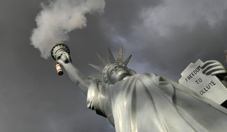 A replica of the Statue of Liberty by Danish artist Jens Galschiot emits smoke in a park outside the 23rd UN Conference of the Parties (COP) climate talks in Bonn, Germany, Friday, Nov. 17, 2017. (AP Photo/Martin Meissner)