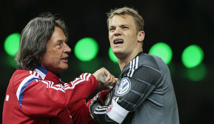 In this Saturday, May 17, 2014 photo Bayern Munich's team physician Hans-Wilhelm Mueller-Wohlfahrt, left, treats Bayern goalkeeper Manuel Neuer during the German Soccer Cup Final between FC Bayern Munich and Borussia Dortmund at the Olympic Stadium in Berlin, Germany. (AP Photo/Markus Schreiber)