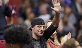 Washington Nationals baseball player and National League Cy Young award winner Max Scherzer waves to the crowd during a break in the action in the second half of an NBA basketball game between the Washington Wizards and the Miami Heat, Friday, Nov. 17, 2017, in Washington. (AP Photo/Nick Wass)
