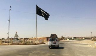 A motorist passes by a flag of the Islamic State group in central Rawah, 175 miles (281 kilometers) northwest of Baghdad, on July 22, 2014. (Associated Press) **FILE**